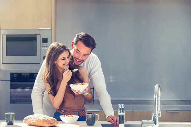 couple having fun eating breakfast. - essen aktuell stock-fotos und bilder