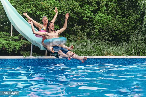 Couple having fun in a swimming pool during summer day
