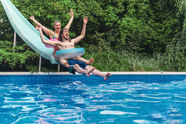 Couple having fun in a swimming pool during summer day stock photo
