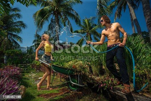 Portrait of couple having fun with garden hose splashing summer rain in garden