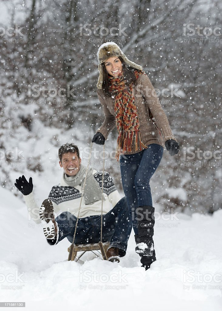 Couple having Fun on Sled in a Snowstorm royalty-free stock photo