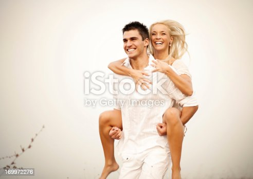 Young man giving his girlfriend a piggyback ride.