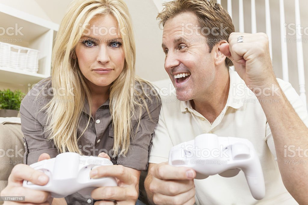 Couple Having Fun Playing Video Console Game Couple, man and woman, having fun playing video console games together. The man has just beaten the woman, he is celebrating, she is annoyed. 30-39 Years Stock Photo