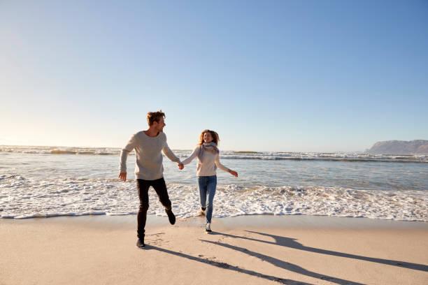 paar loopt langs winter beach samen plezier - mid volwassen koppel stockfoto's en -beelden