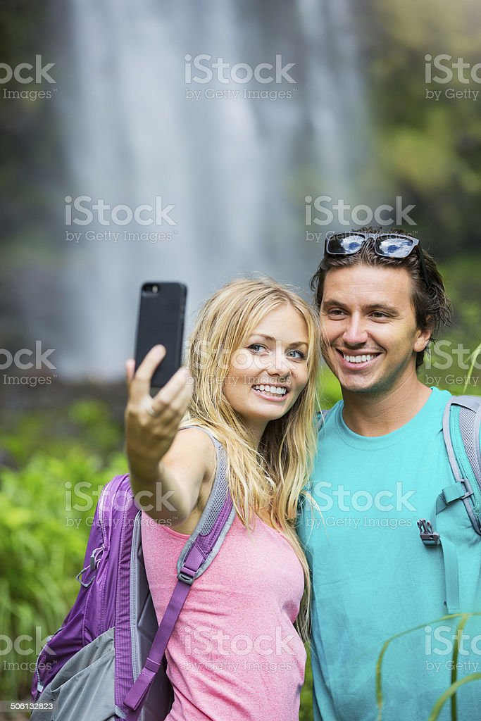 Couple having fun taking pictures together outdoors on hike royalty-free stock photo