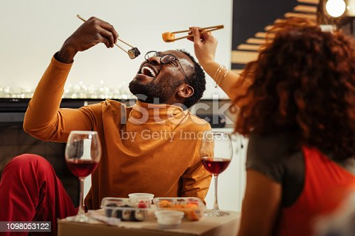 Having fun. Cute loving couple having fun while eating sushi at home after fast delivery