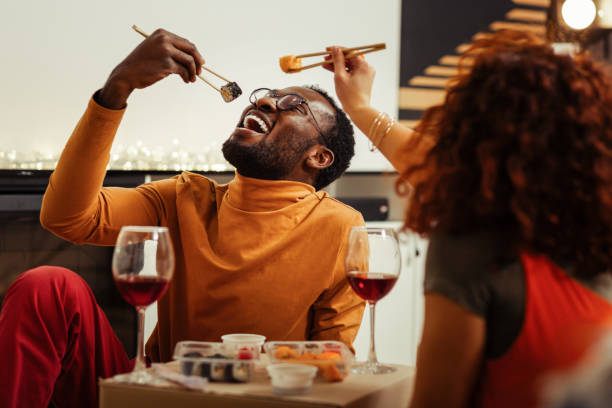 couple having fun while eating sushi at home after fast delivery - sushi stock pictures, royalty-free photos & images