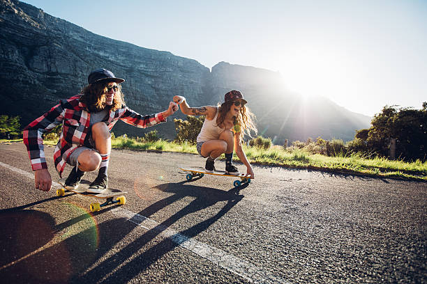 Couple having fun with skateboard on the road stock photo