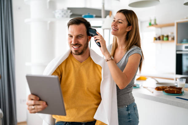 Couple having hair cut at home during quarantine coronavirus pandemic, online hairdressing on tablet stock photo