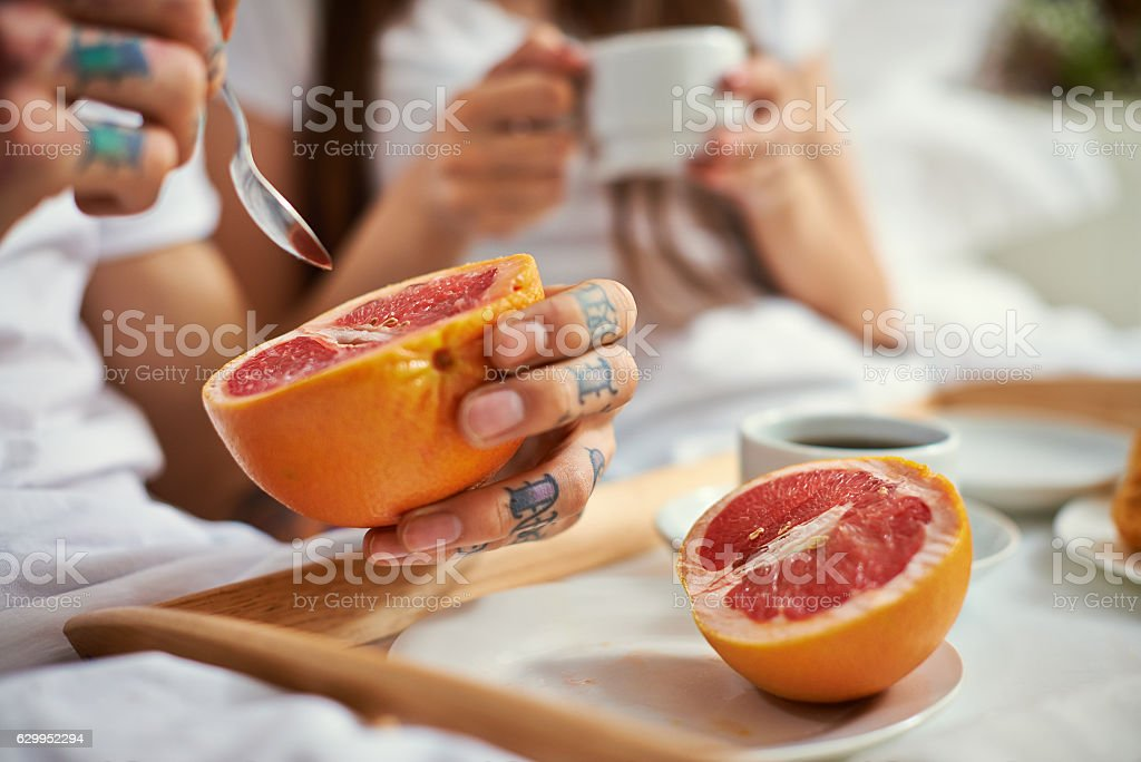 Couple having healthy breakfast in bed, man eating grapefruit stock photo