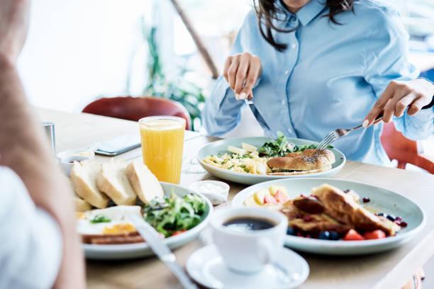 paar beim gesunden frühstück im modernen restaurant. menschen essen zusammen - brunch stock-fotos und bilder