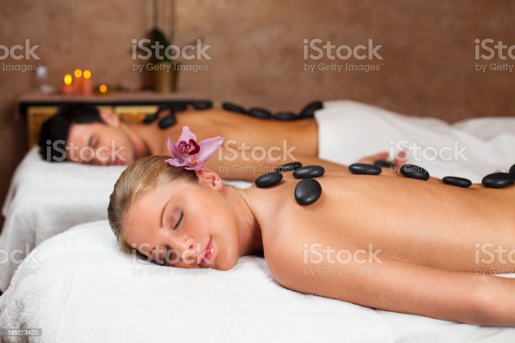 Couple having lastone therapy at spa center stock photo