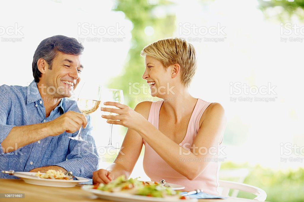 Couple having lunch and toasting with wine glasses royalty-free stock photo