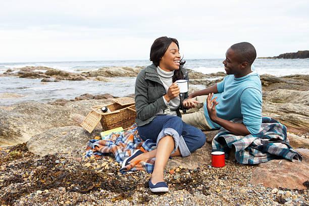 paar mit picknick am strand - romantisches picknick stock-fotos und bilder