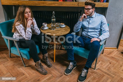 91482522 istock photo Couple having relationship problems sitting in cafe 935695000