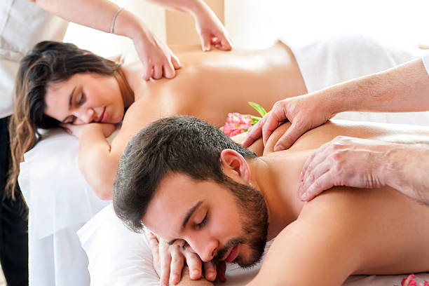 Couple having relaxing body massage in spa. stock photo