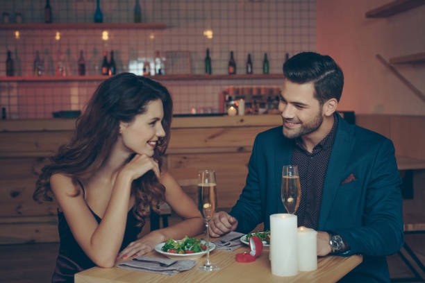 couple having romantic dinner young couple in love having romantic dinner together in restaurant table for two stock pictures, royalty-free photos & images