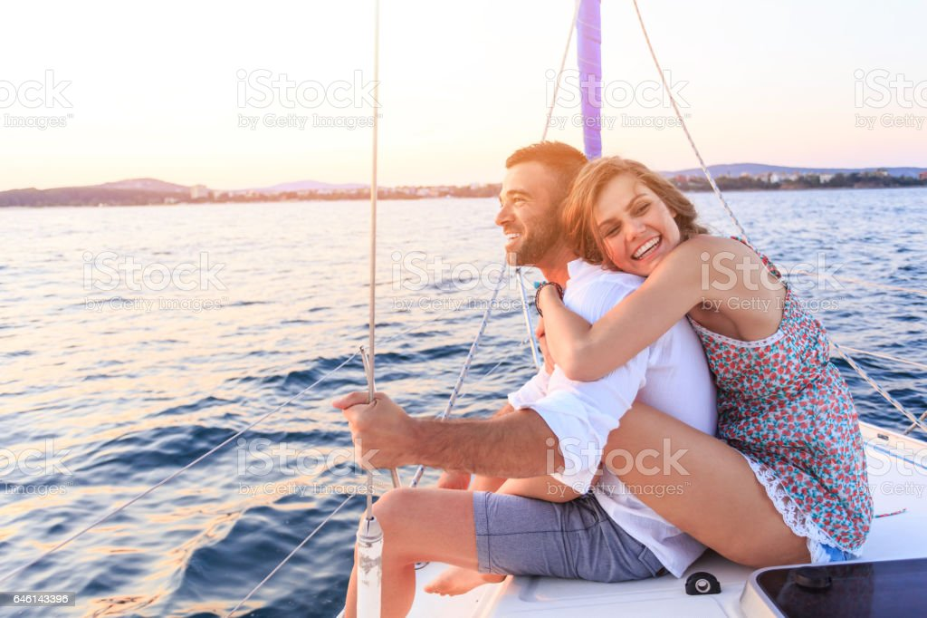 Couple having romantic trip with yacht in sea stock photo