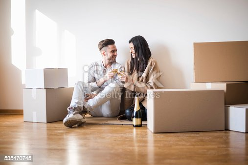 istock Couple having toast on the floor of new apartment 535470745