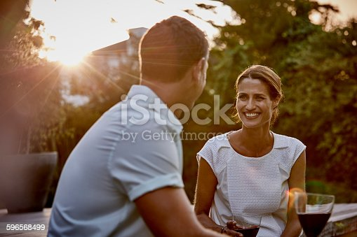 Smiling woman with man having wine on floorboard