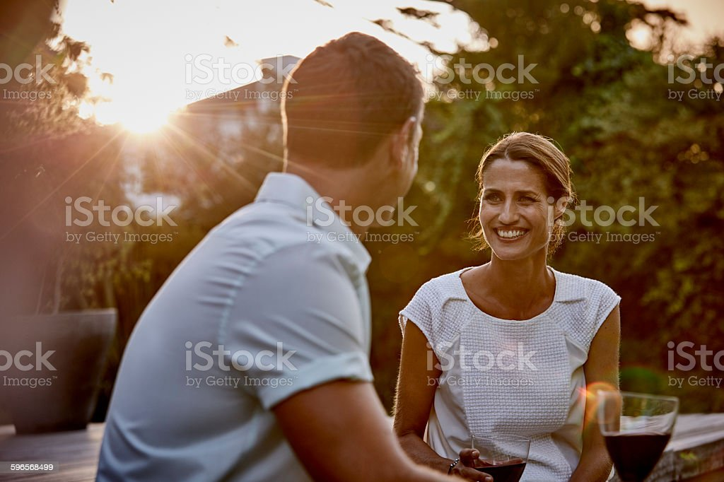 Couple having wine on floorboard stock photo