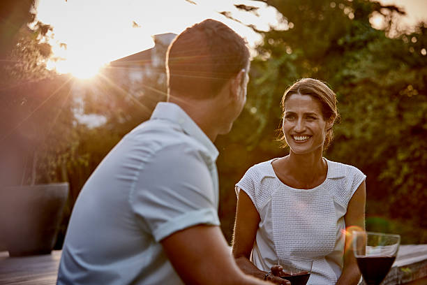 Couple having wine on floorboard Smiling woman with man having wine on floorboard 40 44 years stock pictures, royalty-free photos & images