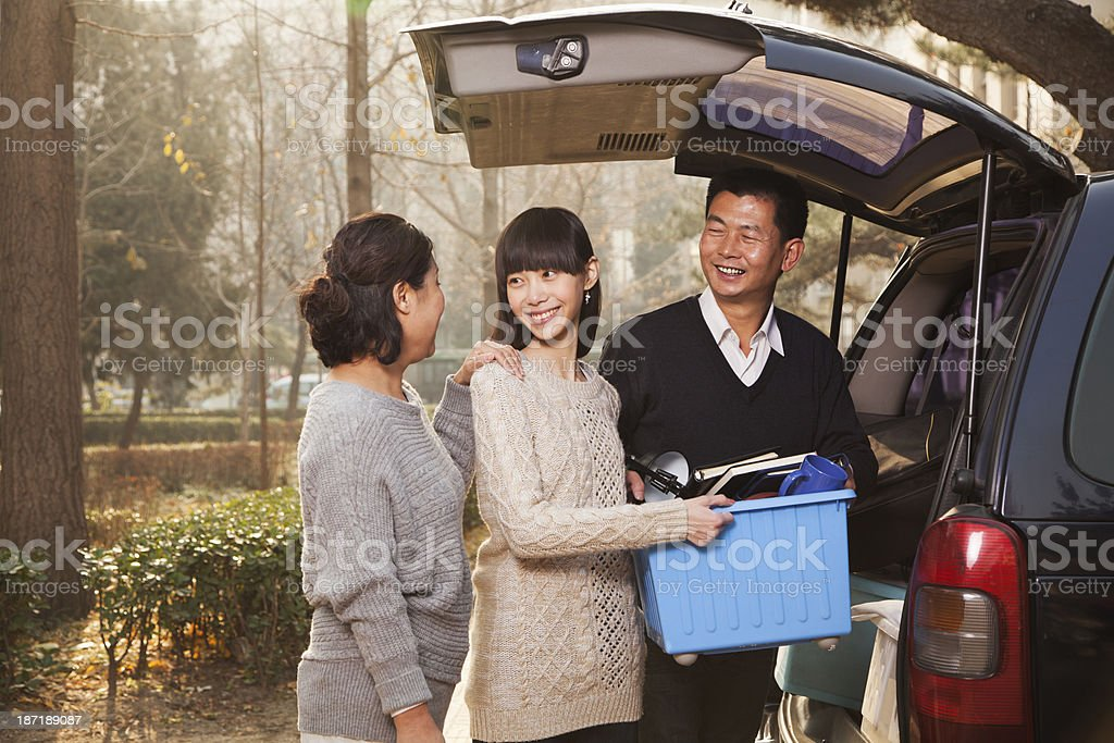Couple helping young woman pack a van for moving to college stock photo