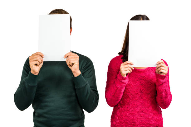 Couple hiding faces with documents stock photo