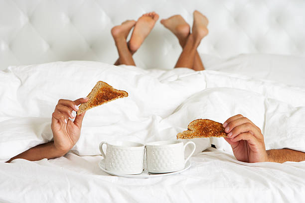 Couple Hiding Under Duvet Enjoying Breakfast In Bed stock photo