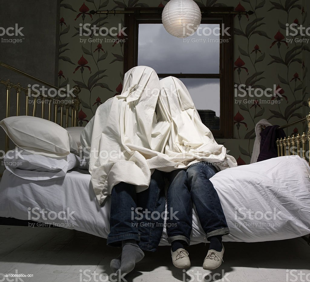 Couple hiding under sheet on bed royalty-free stock photo