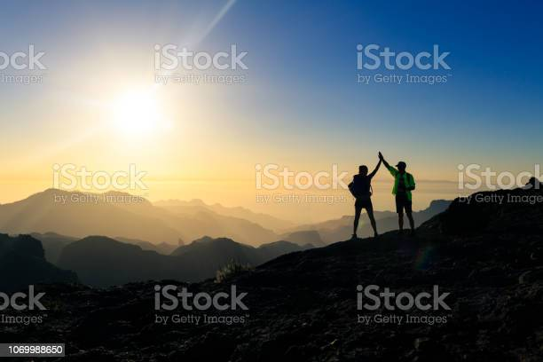 Photo of Couple hikers celebrating success concept in mountains