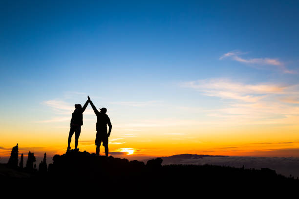 Couple hikers success concept in mountains stock photo