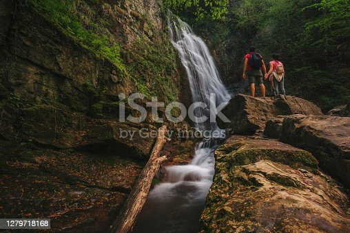 istock Couple hikers with backpacks enjoying view waterfall in rain forest 1279718168
