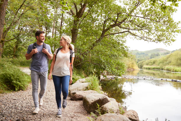 couple hiking along path by river in uk lake district - wędrować zdjęcia i obrazy z banku zdjęć