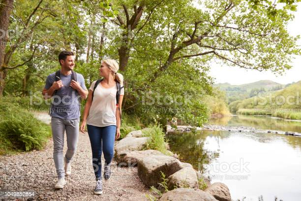 Photo of Couple Hiking Along Path By River In UK Lake District
