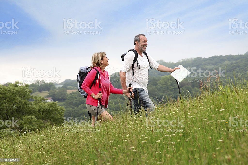 Couple hiking in countryside with map - Royalty-free Active Seniors Stock Photo