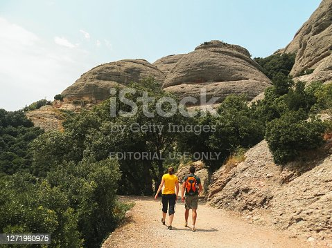 Montserrat, Spain - 01/07/2017: The picture shows a couple in a trail located in Montserrat, Spain. The orange backpack and the yellow shirt stand out.