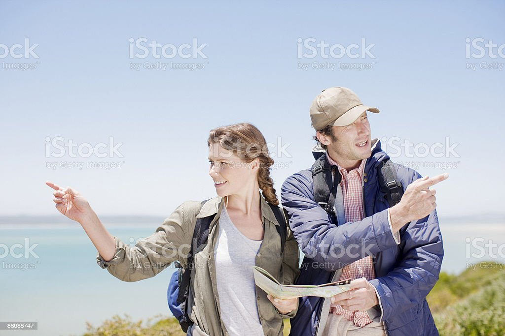 Couple hiking in remote area and looking at map royalty-free stock photo