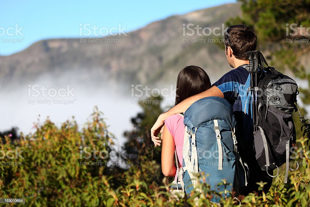 Couple hiking looking at view stock photo