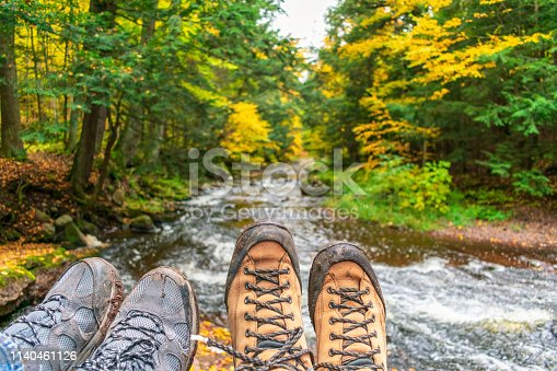 Muddy hiking boots over forest stream in fall - outdoor adventure and recreation