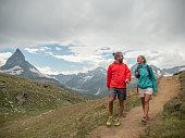 istock Couple hiking on mountain trail, the Matterhorn in distance 1314771900