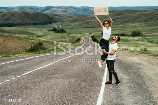 A couple hitchhiking. A man and a woman catch a car by the road. A young couple votes on the road. A man and a woman are hitchhiking. A couple hitch a ride on the road. Hitching a ride. Copy space