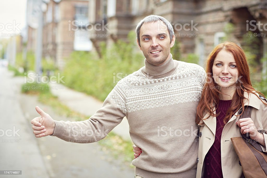Couple hitchhiking on highway royalty-free stock photo