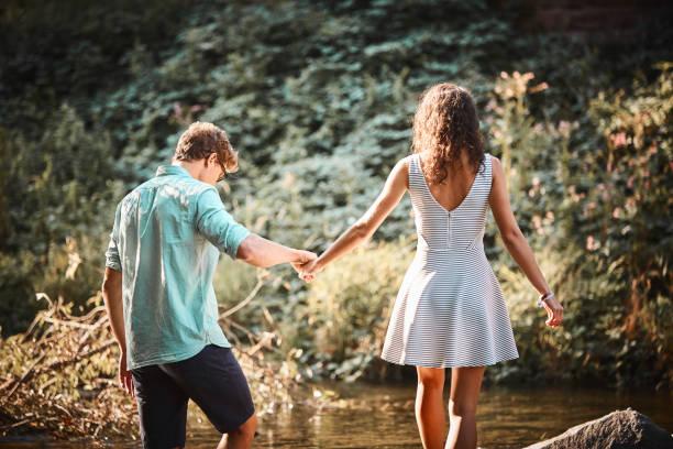 ehepaar hält bei sonnenuntergang hände im strom - sommerferien baden württemberg stock-fotos und bilder