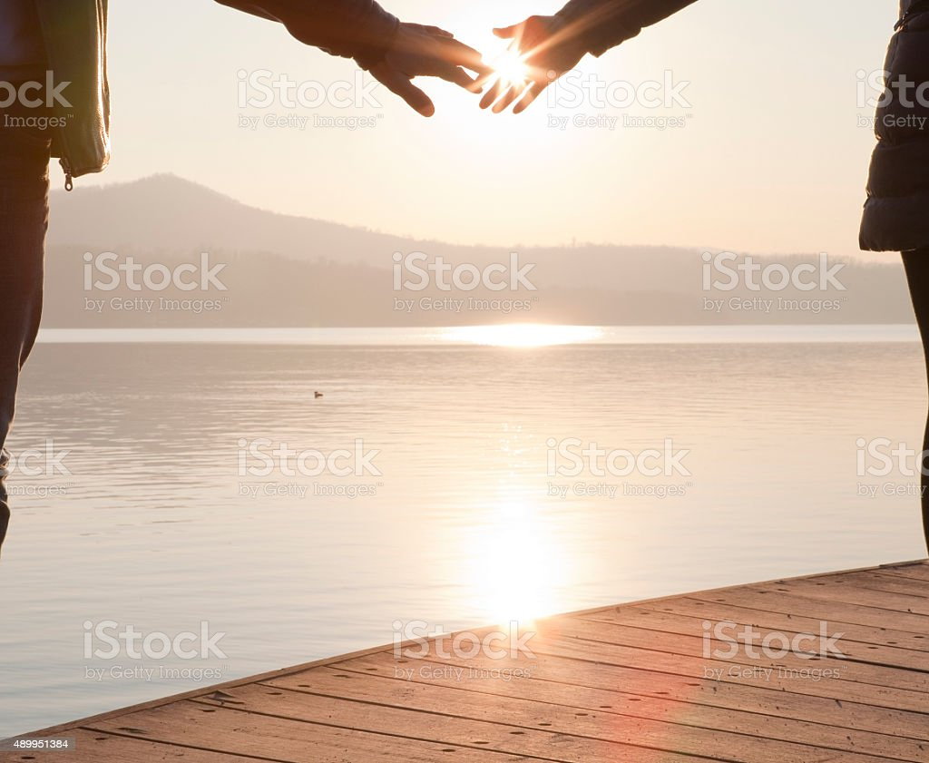 Couple hold hands on wooden wharf above lake, sunrise stock photo