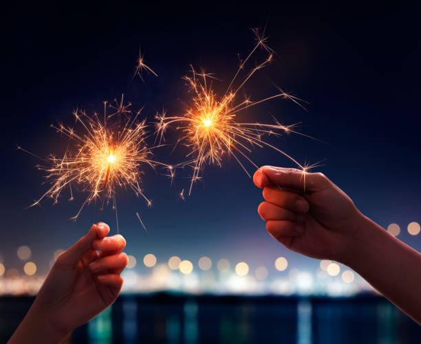 Couple holding a burning sparklers stock photo