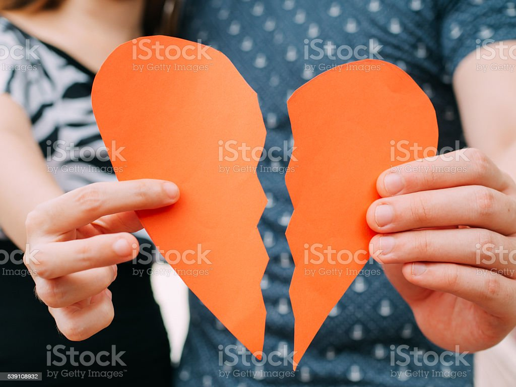 Couple holding a half heart shape breaking apart stock photo