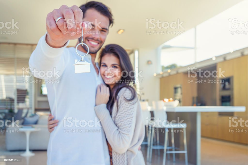 Couple holding a house key in their new home. Couple holding a house key in their new home. They are standing in their new modern house. Both are happy and smiling. The house key has a house icon keyring Adult Stock Photo