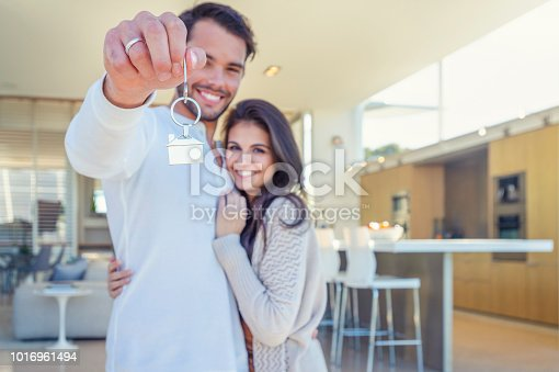 Couple holding a house key in their new home. They are standing in their new modern house. Both are happy and smiling. The house key has a house icon keyring