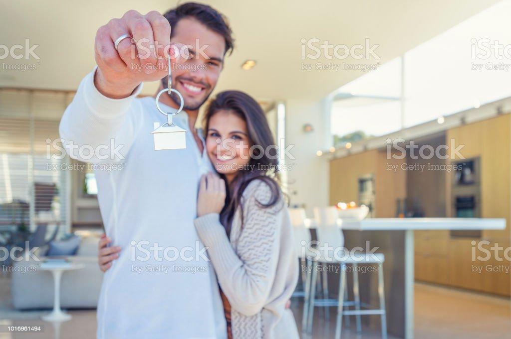 Paar hält ein Hausschlüssel in ihrer neuen Heimat. – Foto
